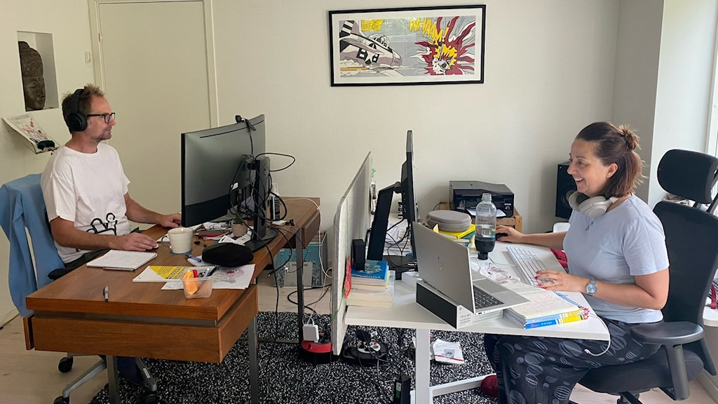 two people in casual clothing sit at desks facing each other. both are looking at their computers, but the woman is smiling. a framed picture of what looks like comic book art is on the wall.