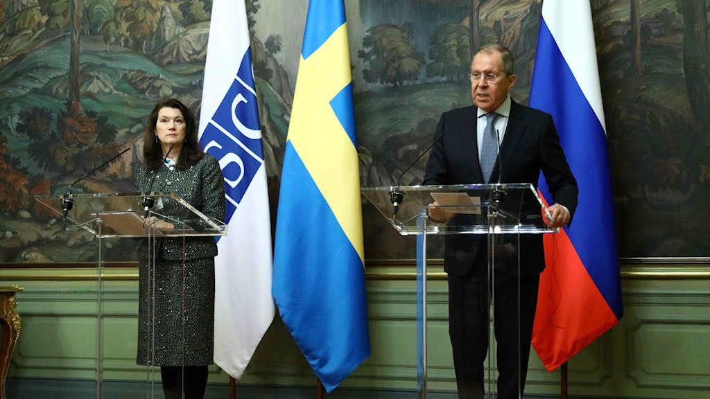 Two people at a press conference, both in front of a huge painting. A woman is standing in front of a Swedish and an OSCE flag and a man is standing in front of a Russian flag.