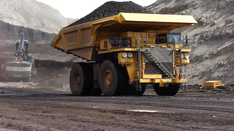 A yellow coal mining truck transporting tons of coal