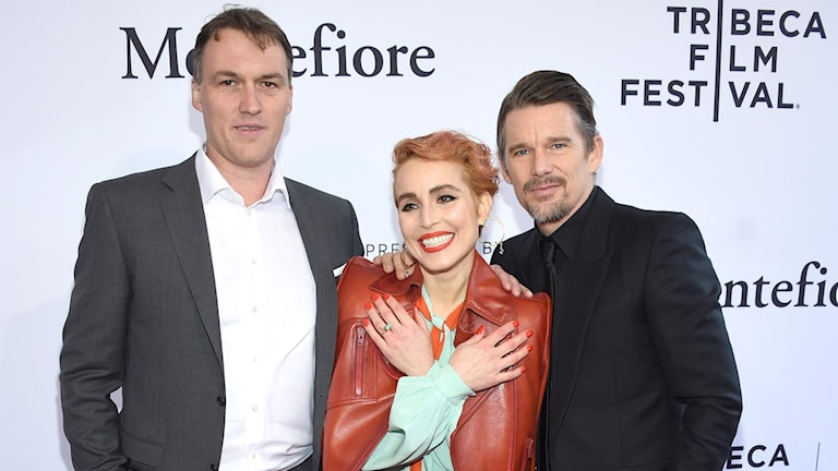 Woman and two men looking into the camera in front of a Tribeca Film Festival backdrop.