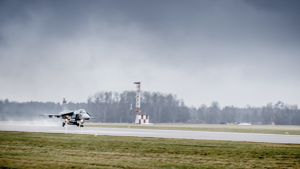 An image of a military jet landing on a runway.
