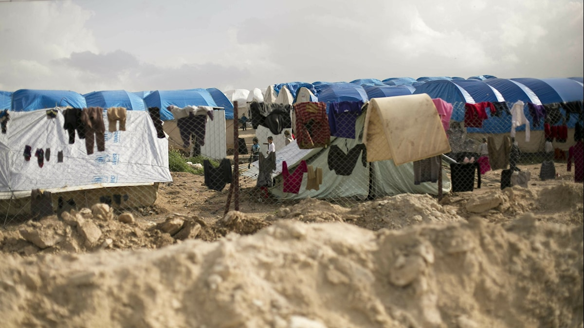 Laundry dries on a chain link fence in an area for foreign families, at Al-Hol camp in the Hassakeh province, Syria.
