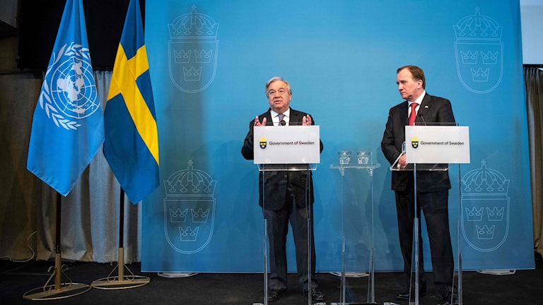 UN and Swedish flags next to the UN Secretary-General and the Swedish prime minister at a press conference,