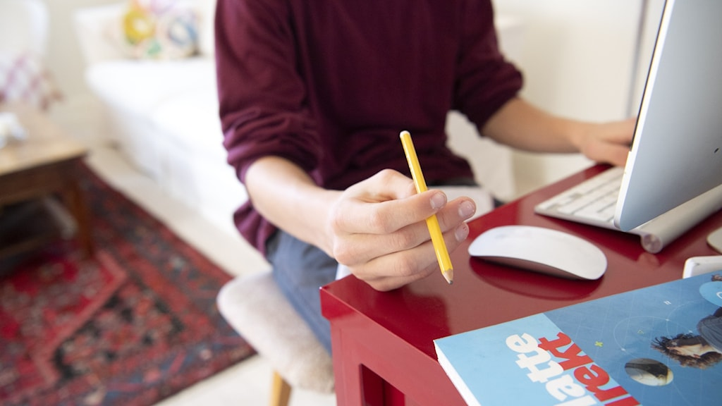 A person sitting at a desk holding a pencil.