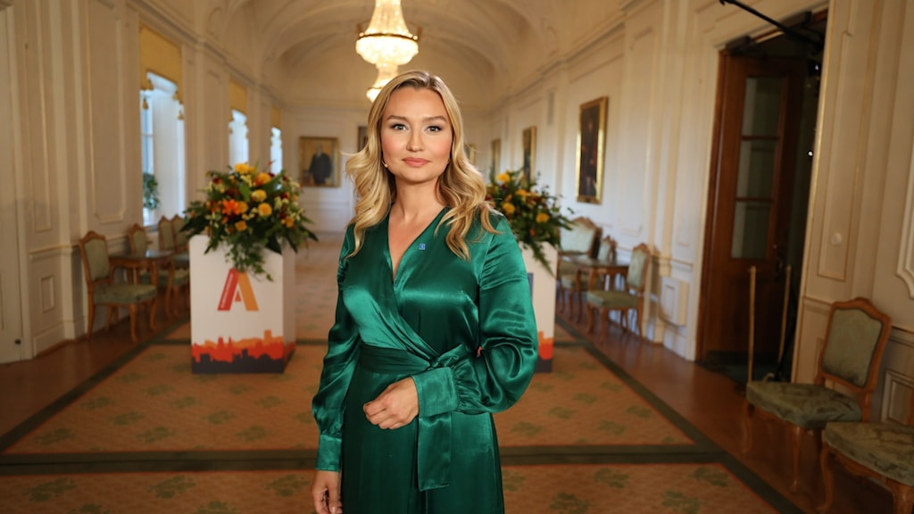 An image of a person wearing a green dress stands stands in a grand room and looks at the camera