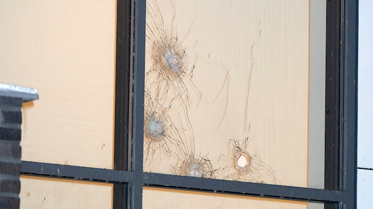 Close-up on a window that has been shot at.