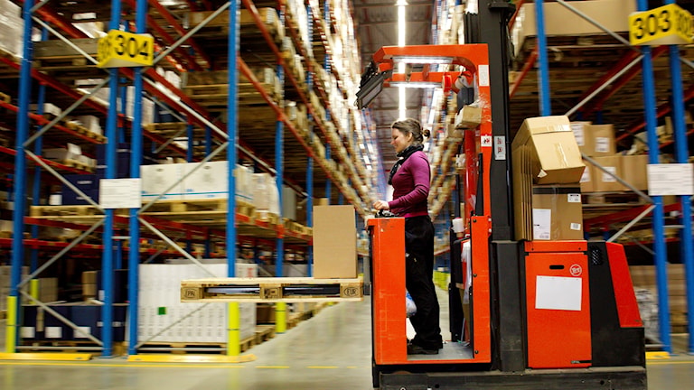 A woman driving a forklift in a warehouse
