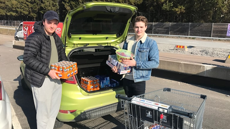 Two young men filling the car with soft drinks and sweets.