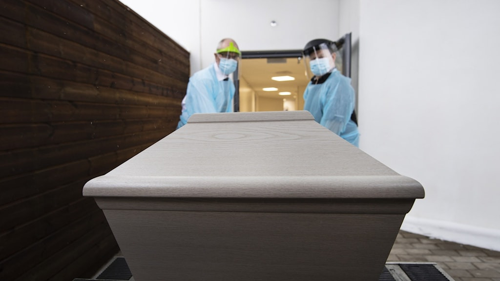 Two people in medical protective gear pushing a coffin.