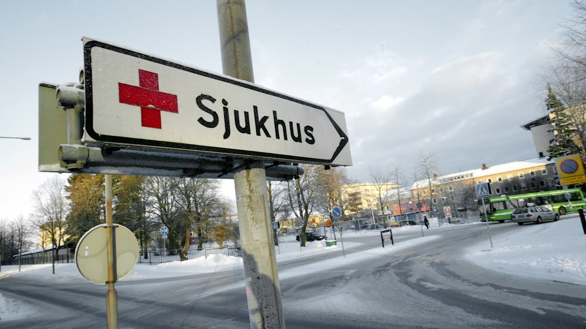 A sign reading sjukhus pointing to the right on a snowy street.