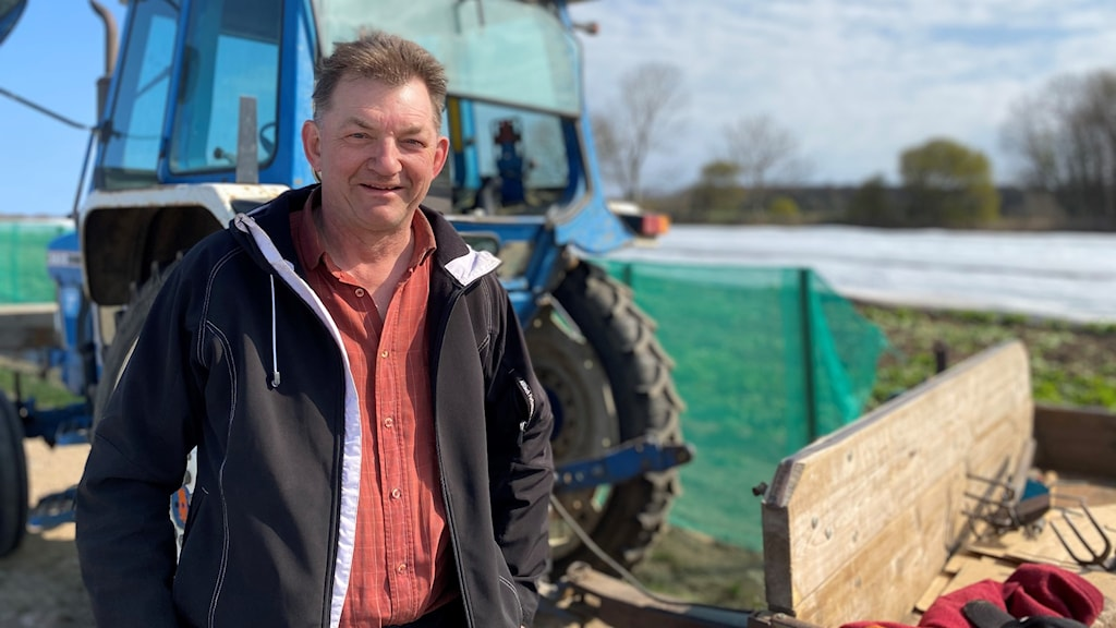 A picture of a man standing outside in front of a farm tractor.