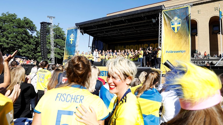 A crowd watches the Swedish women's football team on a stage