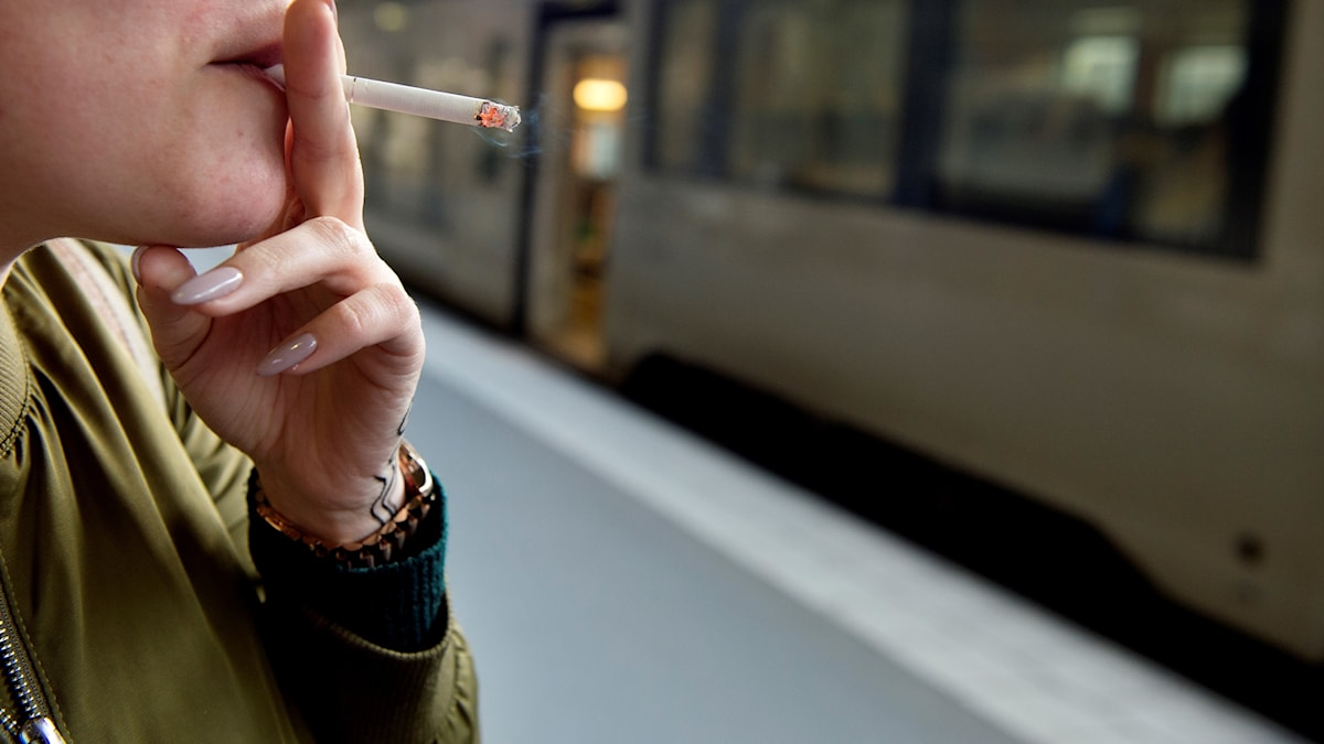 A woman holding a cigarette to her lips.