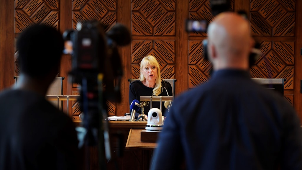 A woman speaking before TV cameras.