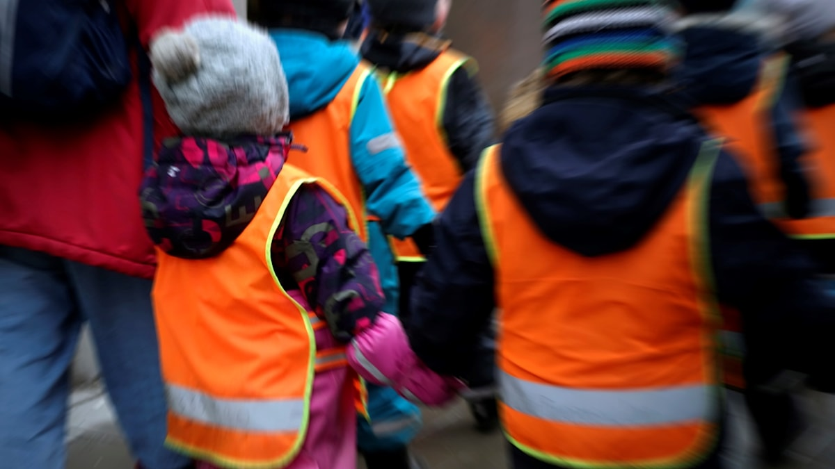 Pre-school kids out for a walk in florescent vests.