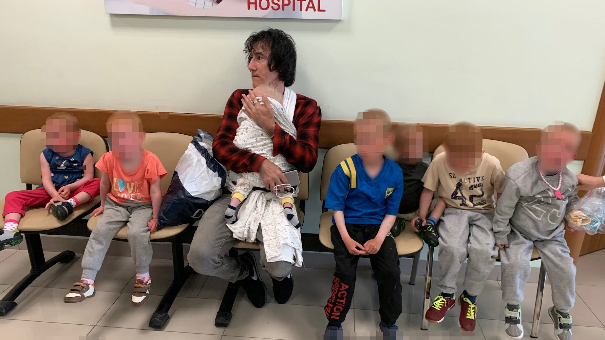 A man with a baby in his arms and six other children sitting next to him, in a hospital waiting room.