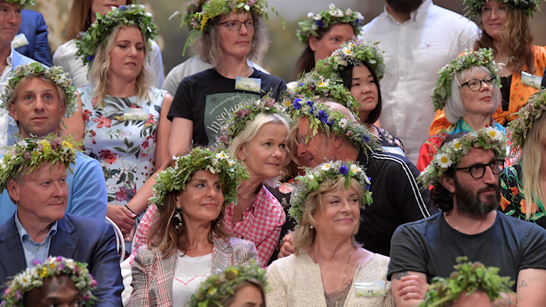 Men and women looking to the right and wearing rings of flowers on their heads.