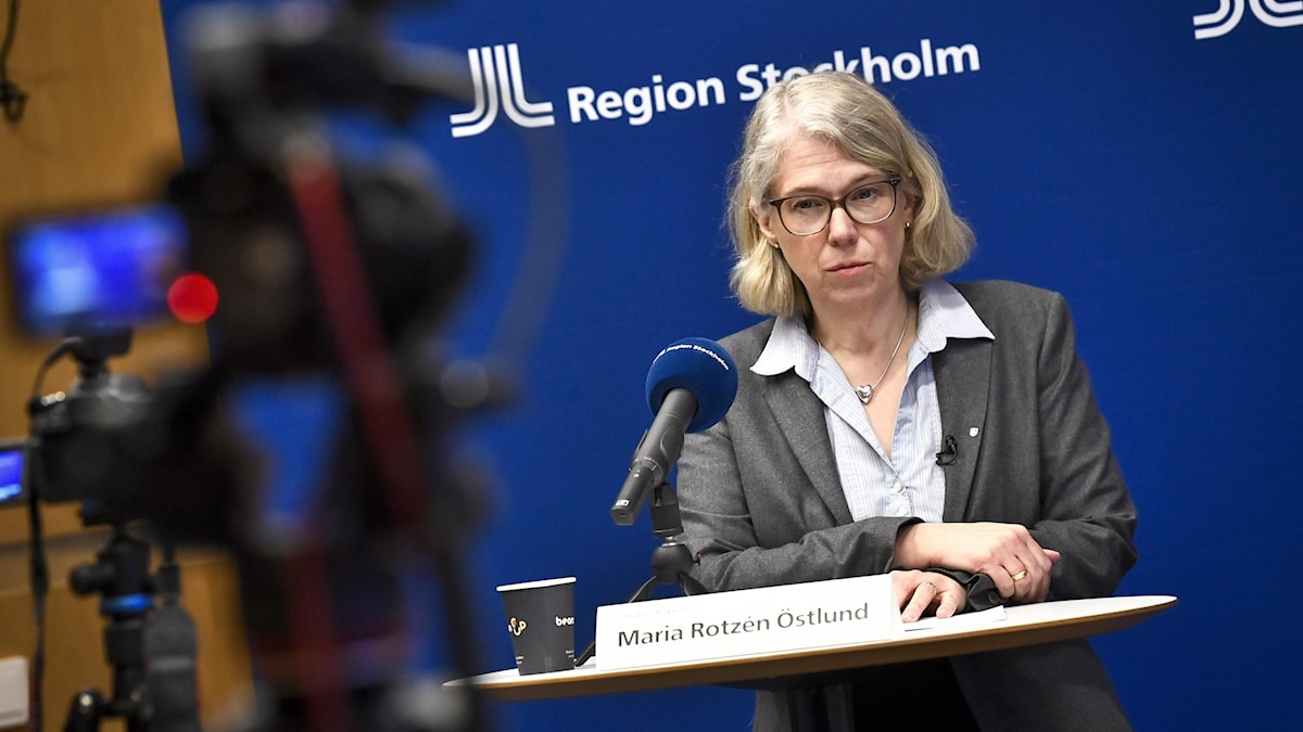 A woman in glasses at a podium with a camera in the foreground.