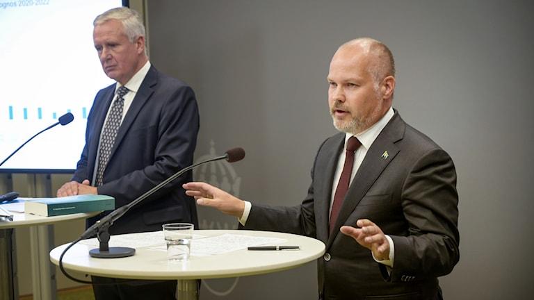 Two men talking in front of microphones