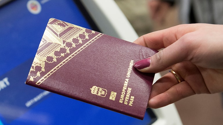Close-up of a hand holding a Swedish passport.