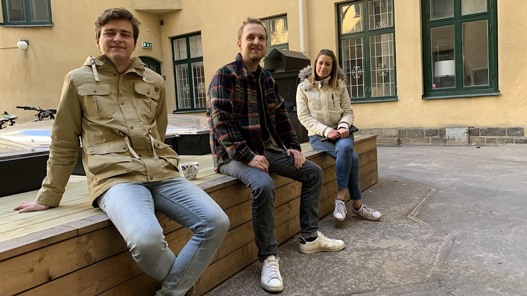 Three people sitting on a wooden bench in a courtyard.