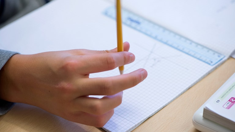 A hand and a pen hovering over a piece of paper.