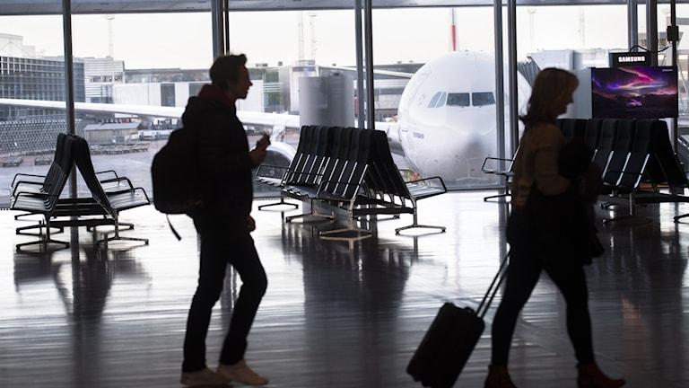 Passengers walking through an airport.
