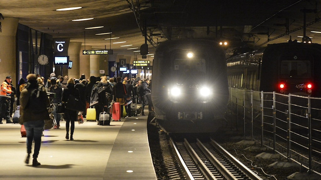 A train station platform full of people with a train on the tracks to the right.