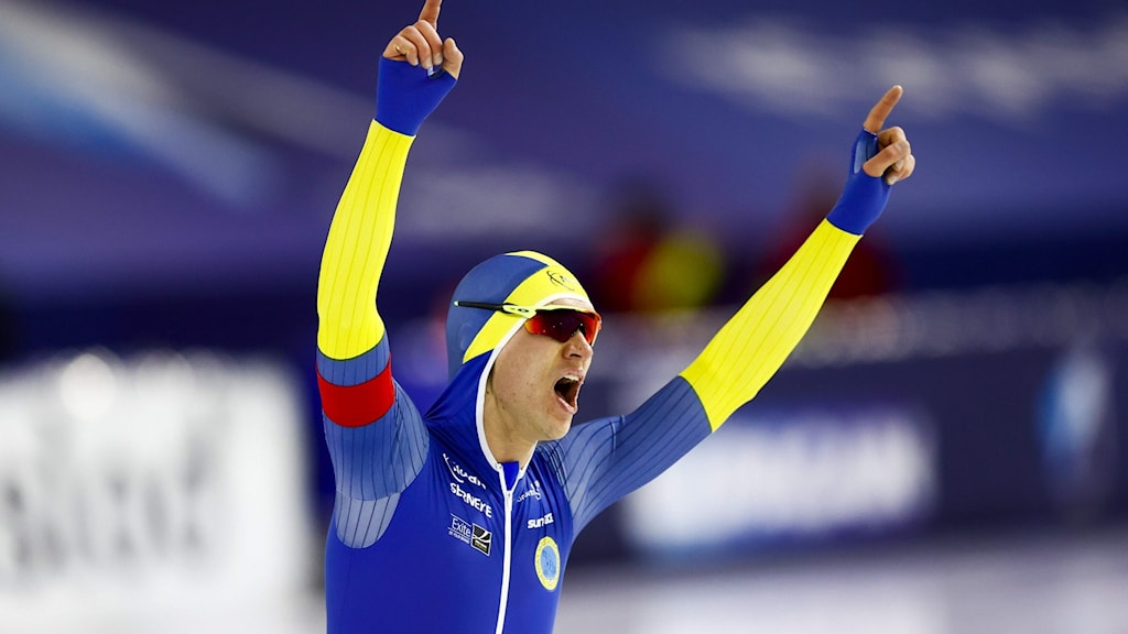 Man in skating glasses and suit raising his arms above the head, cheering.