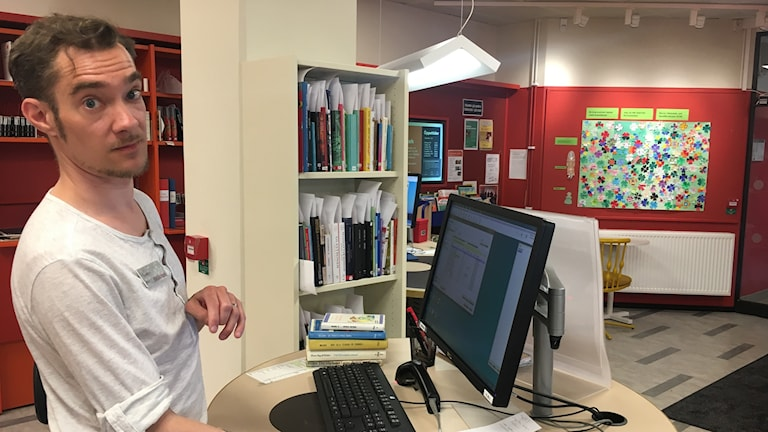 Man in front of a computer, in a library.