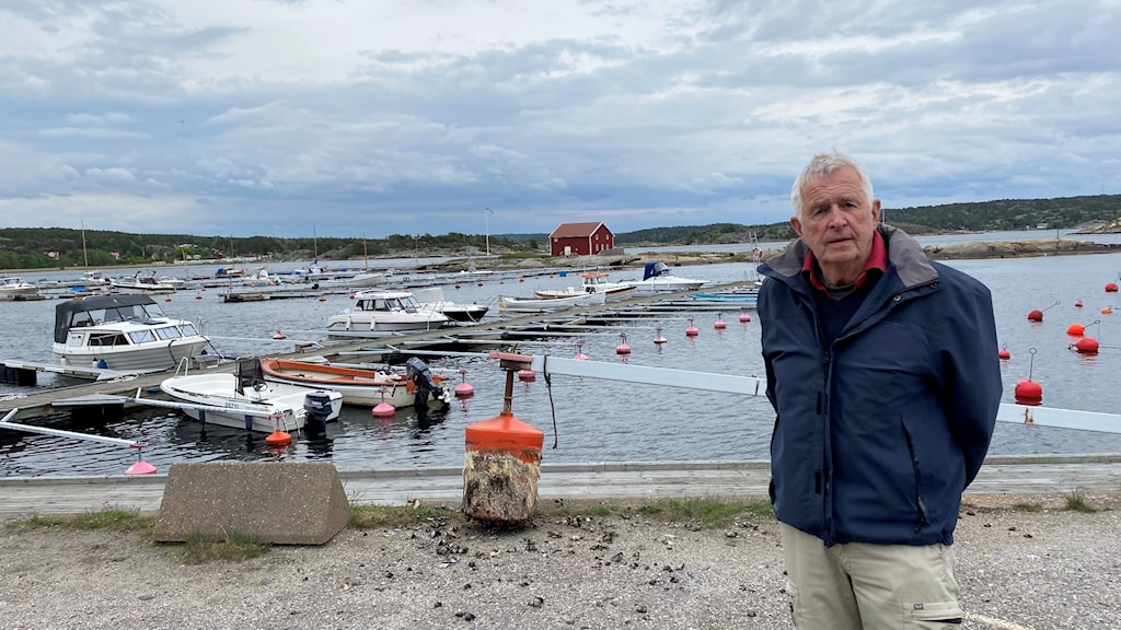 Man in front of a marina where there are hardly any boats.
