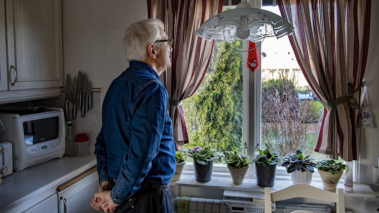 A older man standing in a kitchen starring out a window of a home.