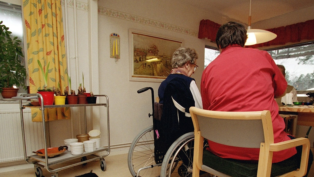 Woman sitting next to an elderly woman in a wheelchair.