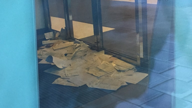 a pile of papers on the floor, just inside the door