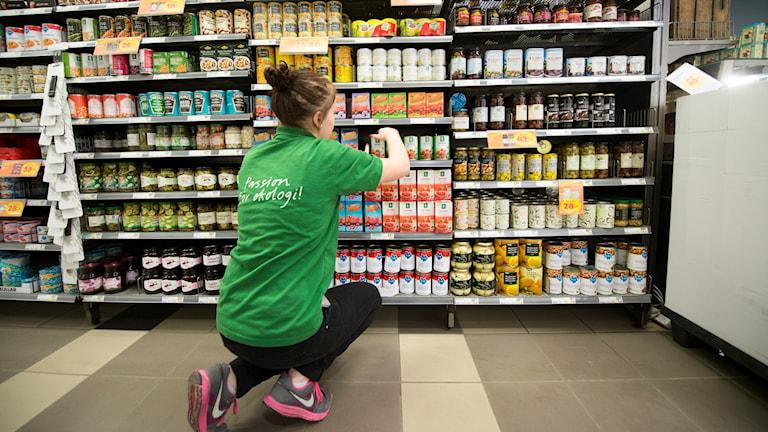 A person filling shelves at a supermarket.