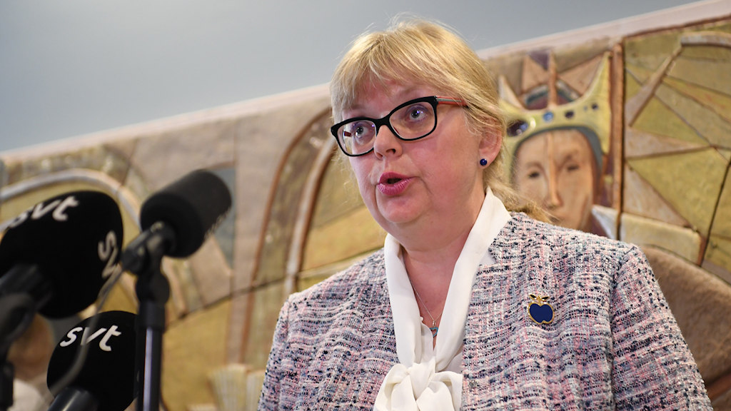 A woman in glasses talking into microphones.