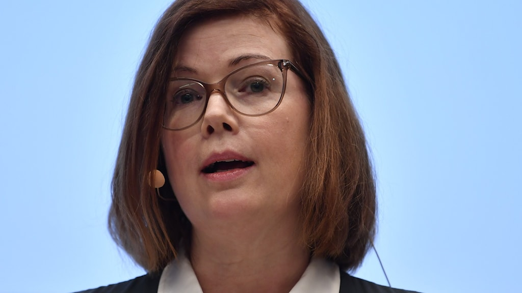 Woman with glasses and a microphone.