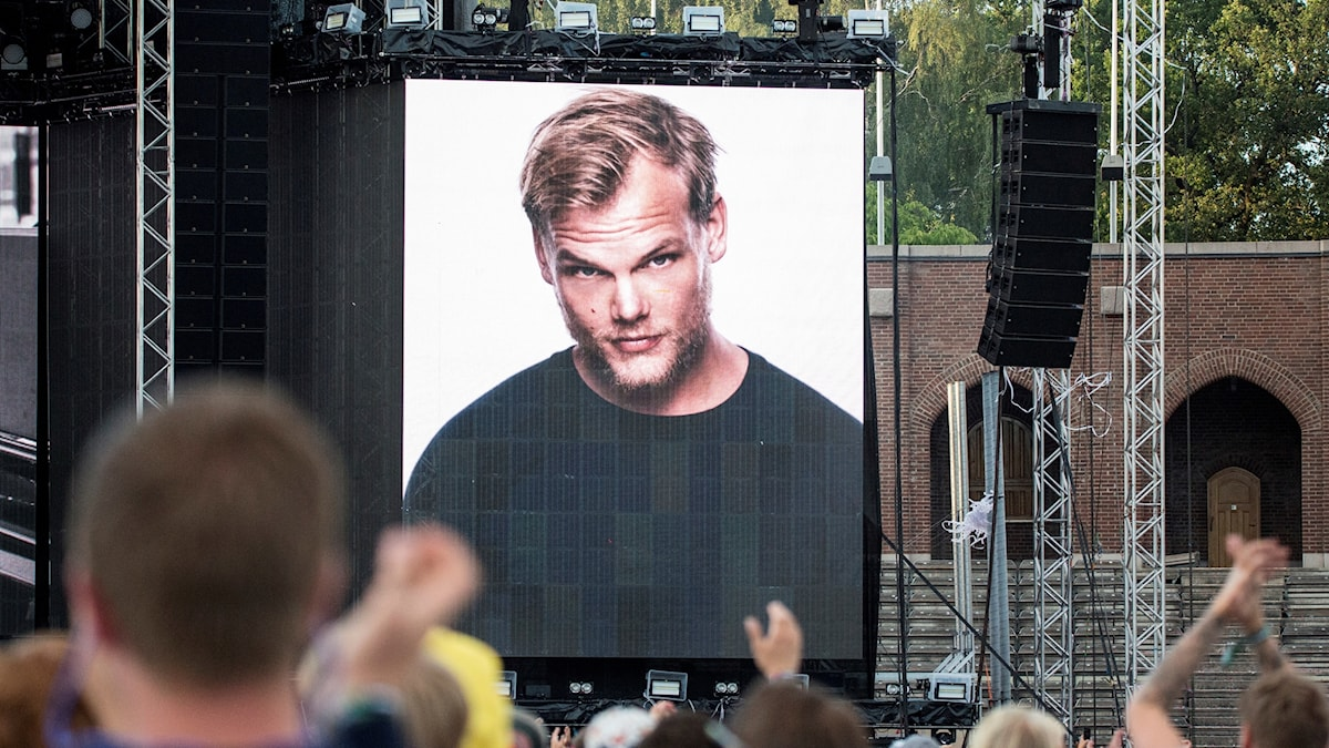 A man's picture on a large tv screen on a stage.