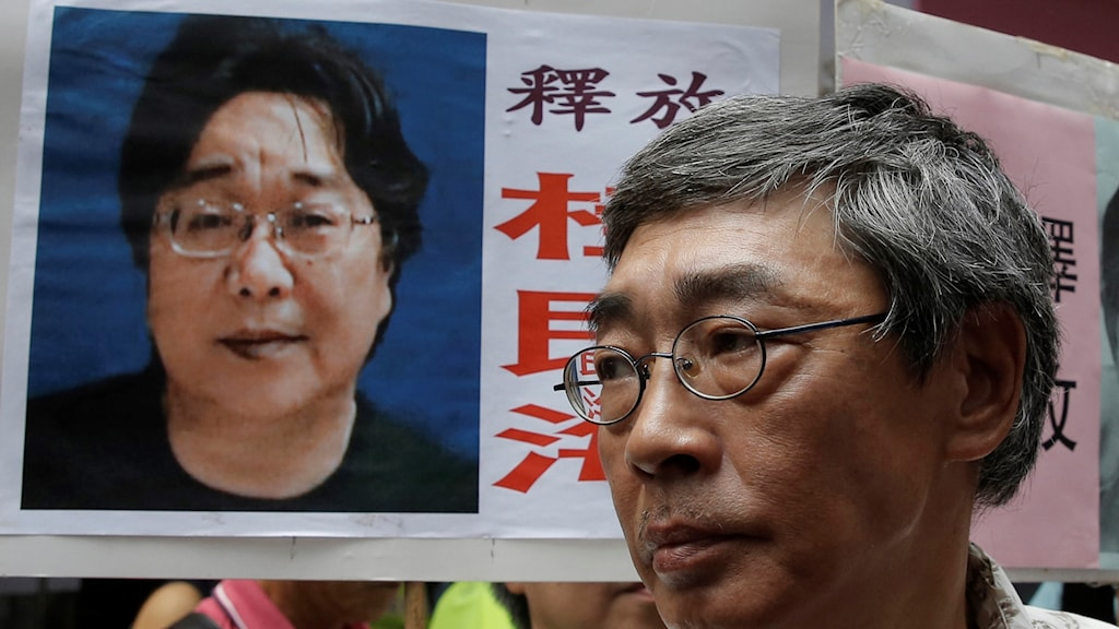 Freed Swede Gui Minhai, left, is featured on a placard during a protest in Hong Kong against the Chinese central government.