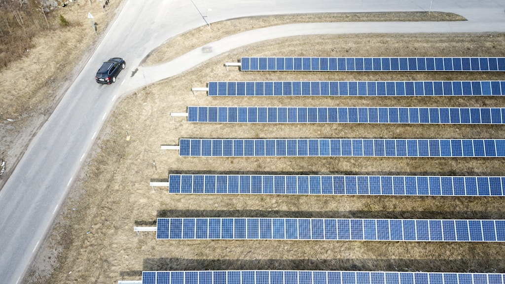 An aerial shot of solar panels in a field next to a road.