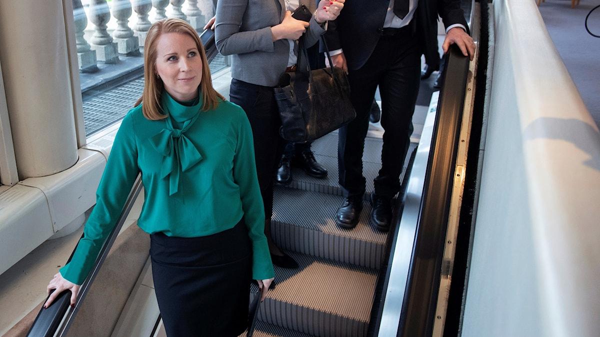 A woman going down on an escalator.