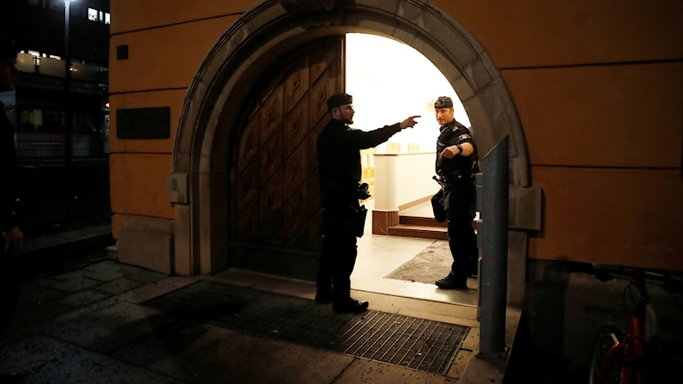 two police stand in an archway