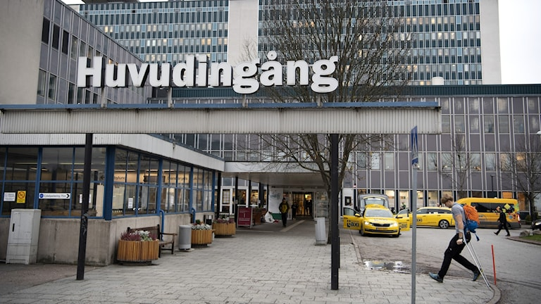 The entrance to a large building with taxis outside the doorway.