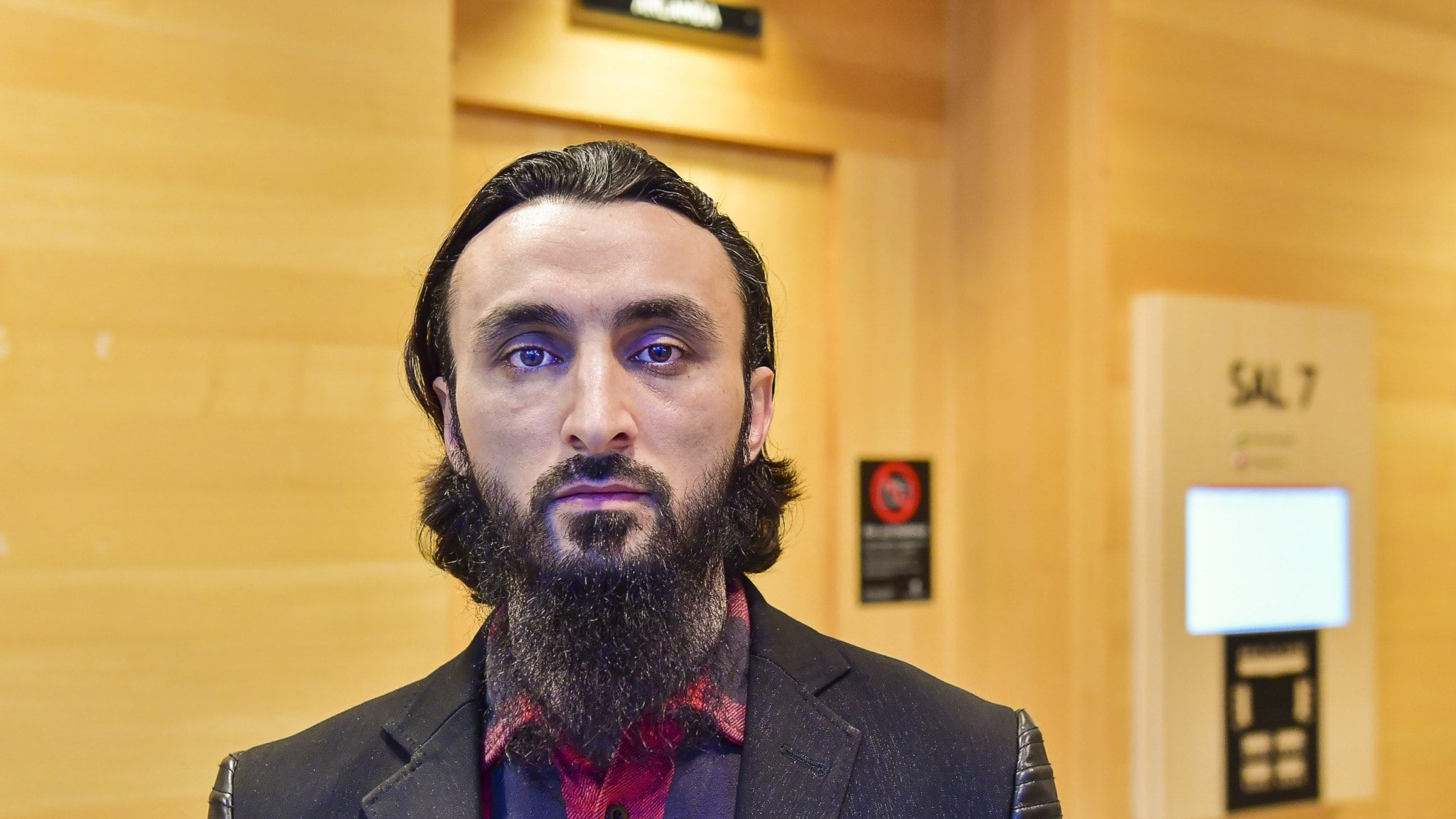 Bearded man in a suit outside a court room.