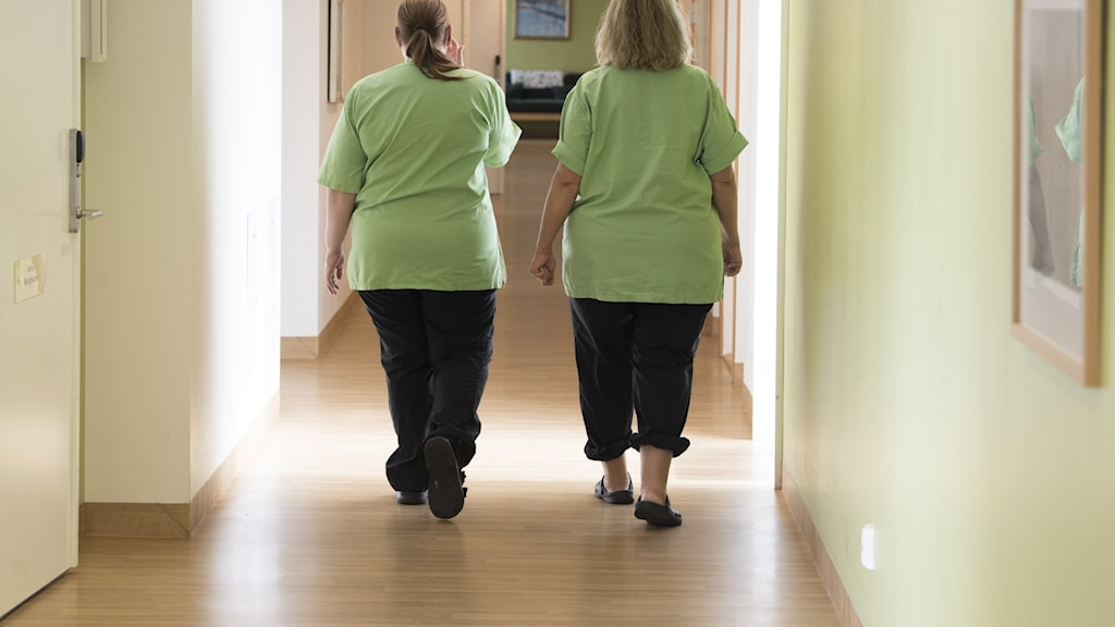 Two auxiliary nurses walking along a corridor