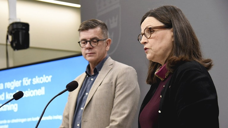 A bespectacled woman and man standing before two microphones.
