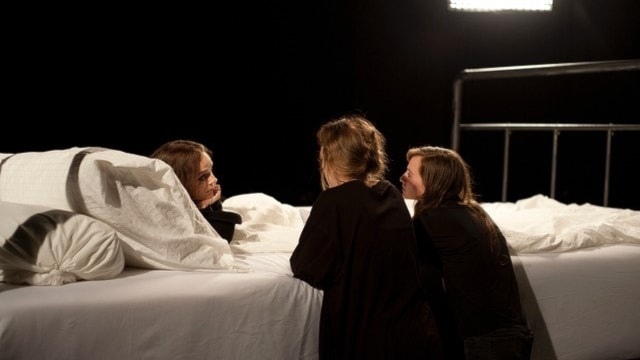 Two women talking to a man on a giant bed.