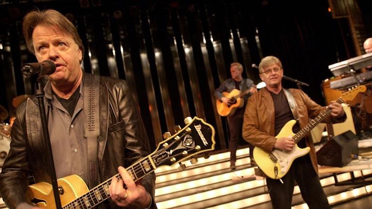 Sven-Erik Magnusson playing guitar with bandmates.