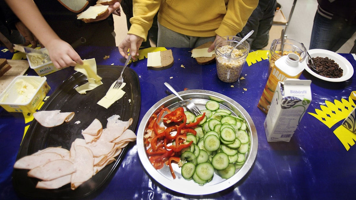 A table with food at a school, children's hands making a sandwich.