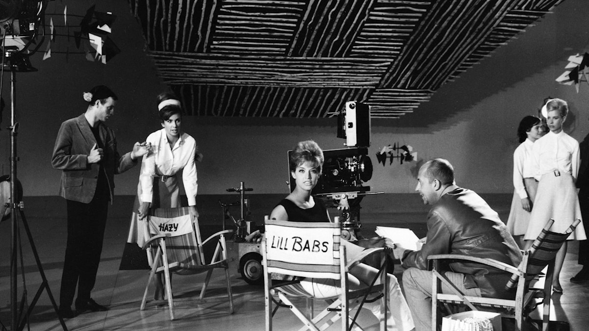black and white photo of a glamorous woman sitting in a chair with the name Lill Babs written on it. She's surrounded by lights and a camera, and other people.